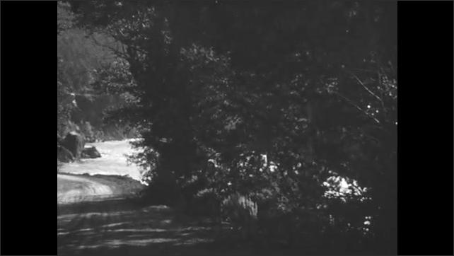 1930s: Car drives along dirt road next to mountains, lake.