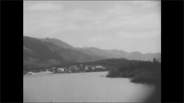 1930s: Town of Skagway, Alaska on the shore of a lake. Snow-covered mountains and tree-lined shore viewed from a boat.