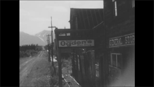 """1930s: A small Alaskan town. Signs on a building read """"General Store"""" and """"Ogden's Cut Plug."""" Dirt road and hills."""