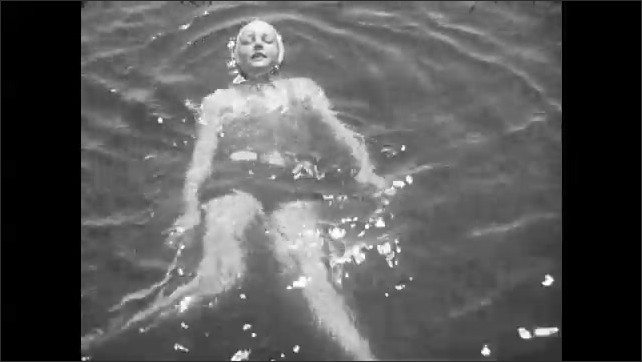 1930s: Woman treads water and swims.  Woman puts on bathing cap.  Man dives off dock.