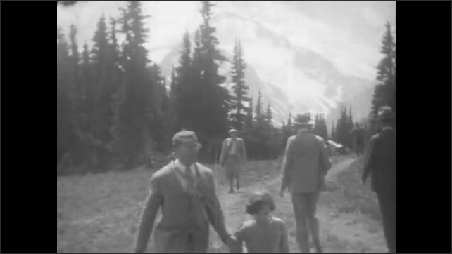 1930s: People stand together in group and look around.  People walk along path in front of mountains.