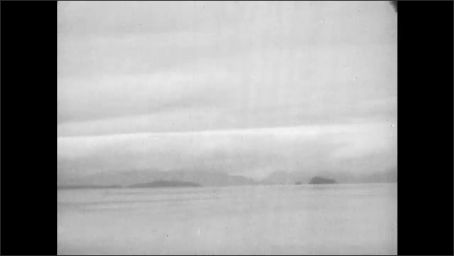 1930s: Mountains along shoreline.  Camping resort.  Small boat speeds by.