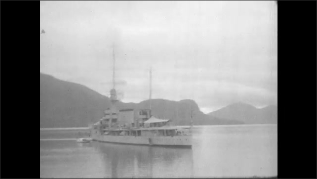 1930s: View of sign, tilt down to group of people. View of building across river. Boat on river, pan across hills, smaller boat enters frame.