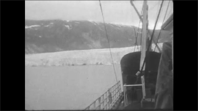 1930s: View of mountains and glacier from ship, pan to deck. Views from ship deck. People on deck, people wave to camera.