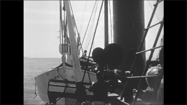 1930s: View from ship, crew lowering lifeboat.