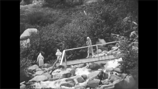1930s: View of river. Women and girl cross bridge over waterfall. Close up of falls. Girl walking on rocks.