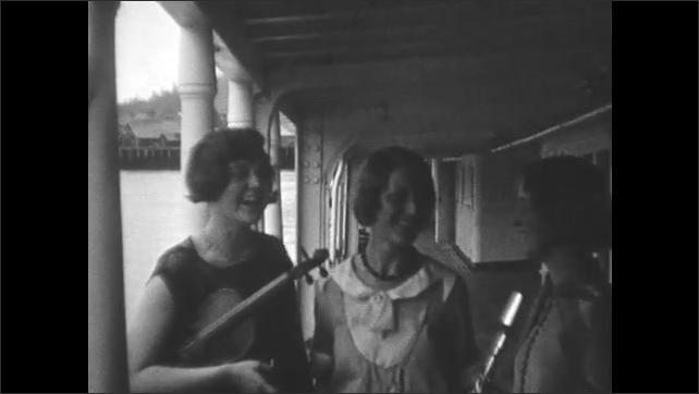 1930s: Women pose on ship deck with musical instruments.
