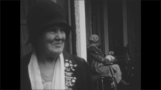 1930s: Close up of woman talking, woman in background with baby. Train drives past camera.