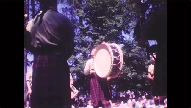 1950s: Scottish pipe and drum corps perform on stage. Man waves and spins drum sticks.