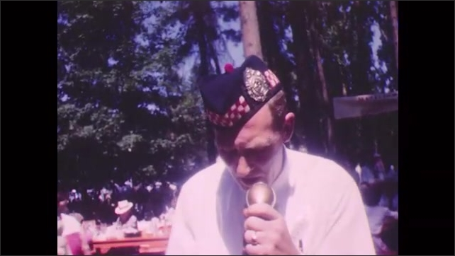 1950s: Scottish pipe and drum corps perform on stage. Sign on picnic table. Man speaks into microphone. Man plays bagpipes. People gather at picnic table.