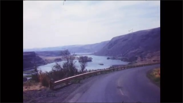 1950s: Tourist sign. Large body of water in mountain basin. Car drives along river highway. People sit near and wade in large body of water.