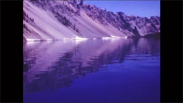 1950s: Mountain along lake, reflection in water. Rippling reflected lake surface.