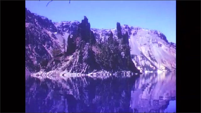 1950s: Rippling water around small tree trunk in lake. Wood of tree trunk, reflection in water. Wood and rock formations in lake cove. Small island in lake, mountains beyond.