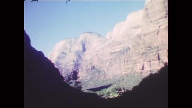 1950s: Canyon view from side of road. Car emerges from tunnel on winding road. Towering stone peaks against blue sky.