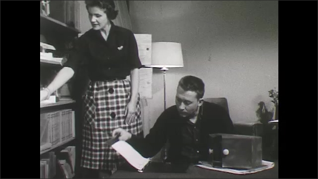 1960s: Man in living room looks at binder. Woman places small shoes on shelf of memorabilia. Woman grabs objects from shelf and shows them to man.