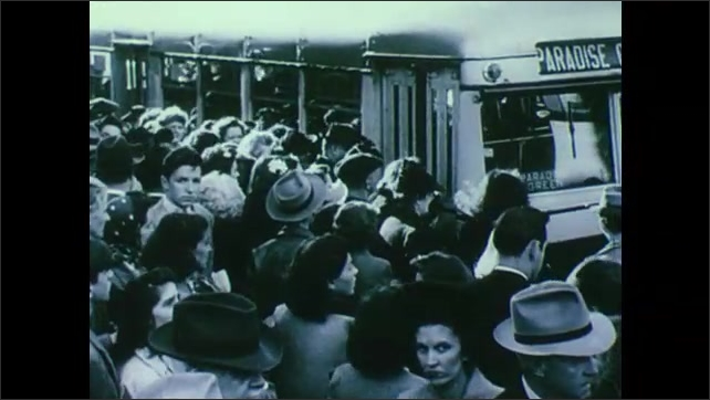1940s: UNITED STATES: play flies above steam train. Defence towns and employment. Populations double during war time efforts. Bus to Paradise Green. People on sidewalk in city.