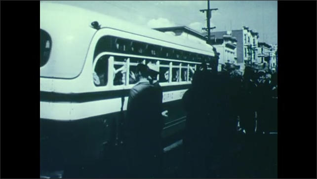 1940s: UNITED STATES: bus takes Japanese people away from homes during 1942. People wave at coach.