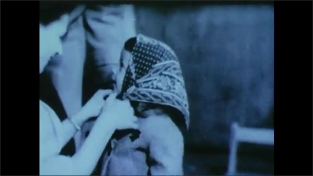 1940s: UNITED STATES: family life during war. Lady kisses child. Child with scarf on head.