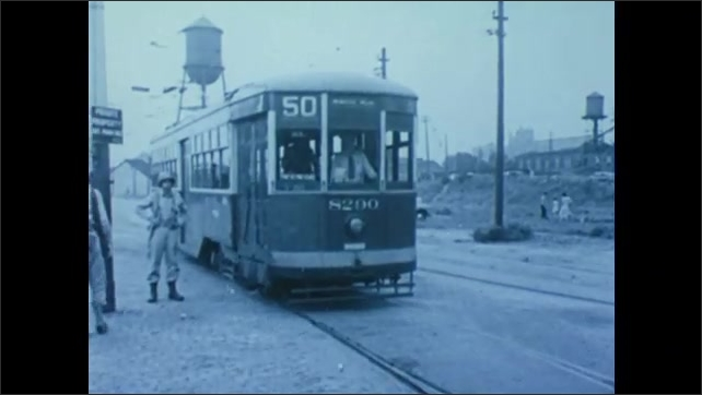 1940s: UNITED STATES: army vehicles in street. Black soldiers board trolley carts. People get on tram.