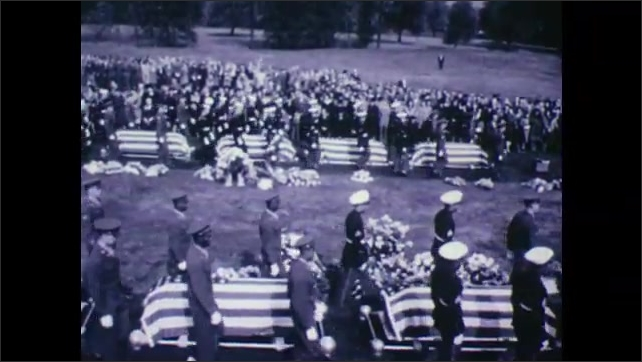 1940s: UNITED STATES: coffins covered in American flags. Grieving widows at funeral.