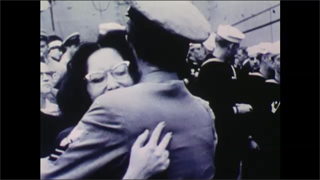 1940s: UNITED STATES: lady kisses sailor by ship. Sailor hugs lady. Sailor picks up son.