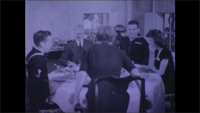 1940s: UNITED STATES: family dinner. Lady serves roast at table. Man says grace. Photo of home. Sailor at table.