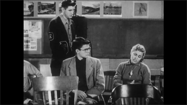 1950s: Dark room with film projector.  Teenage boy turns on lights and speaks.  Girl speaks.
