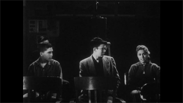 1950s: Teenagers sit in darkened room with film projector.  Boy sits.  Girl speaks and points.  Boy turns on projector.  Boy speaks.