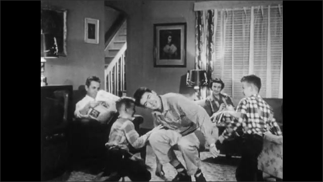 1950s: Living room.  Teenage boy wrestles with brothers.  Mother sews.  Father reads newspaper.  Boy puts on glasses and looks over father's shoulder.
