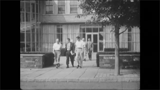 1950s: UNITED STATES: sign for Bell Telephones. Building in street. Bell Telephone Laboratories. Men leave building. Scientists work in lab