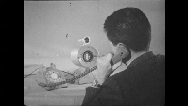 1950s: UNITED STATES: hand picks up telephone. Man turns up volume on telephone. Telephone central office. Lady works with computers
