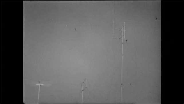 1950s: UNITED STATES: Man presses buttons on radio. Radars move. Tower and sky