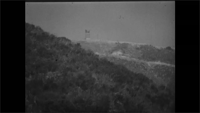 1950s: UNITED STATES: Radio relay system. Tower on ground. Man listens to signals on radio