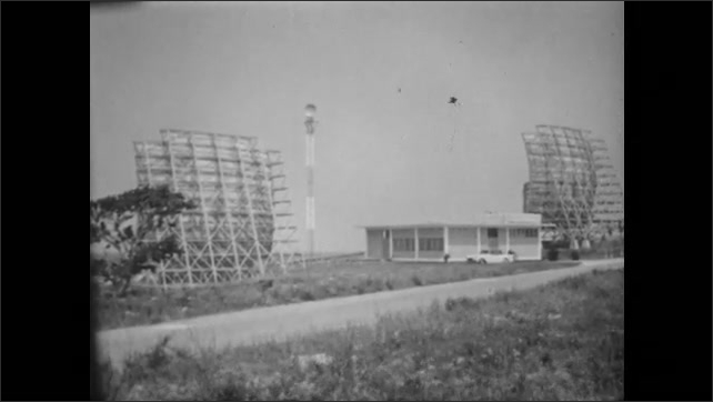 1950s: UNITED STATES: Man sits at desk in office. Office in Havana. Lady listens to calls. Antenna pick up signals. View across station and antenna