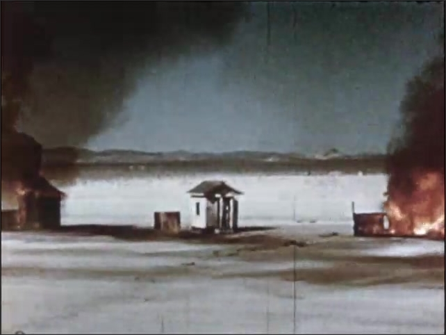 1950s: UNITED STATES: huts catch fire in desert. Flames around house. Painted house in desert. Cloud over desert
