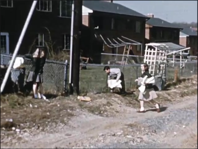 1950s: UNITED STATES: lady speaks to children in school. Children clean up rubbish from yards. Man hits nail with hammer. Lady plants flowers in garden