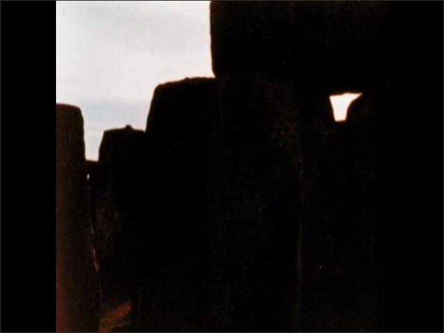 1970s: Sunrise over Stonehenge. Sunlight streams between monoliths at Stonehenge.