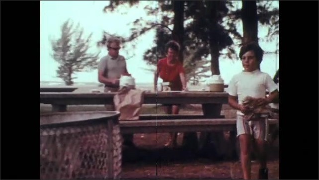 1970s: Kids eating at outdoor table. Close up of girl. Kids throw garbage in trash can, zoom out of can.