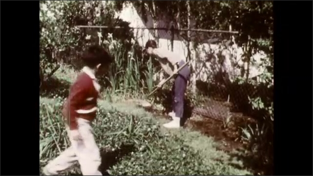 1960s: UNITED STATES: hand pats down soil. Boy's face. Lady watches boy in garden. Boy laughs at mother