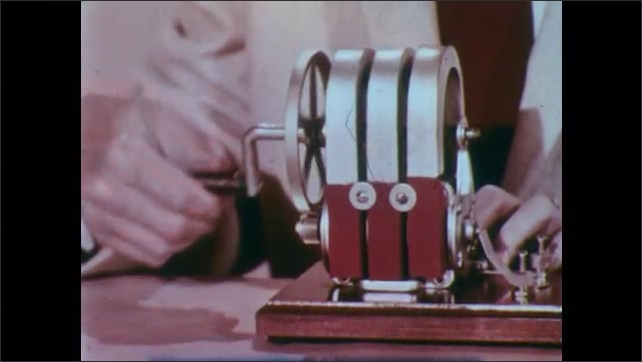 1950s: UNITED STATES: hand removes shaft and crank from generator. Hand spins coil. Magnetic lines of force. Current flows through wire