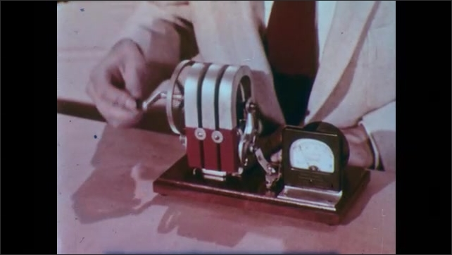 1950s: UNITED STATES: hand attaches monitor to generator. Hand turns crank on shaft