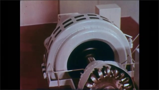 1950s: UNITED STATES: model of water wheel and generator shaft. Hand turns crank on generator