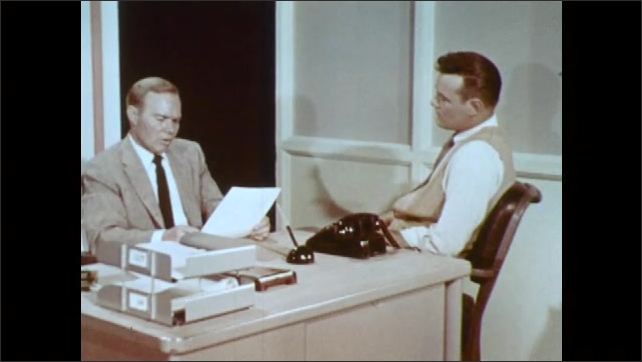1960s: UNITED STATES: boss talks to man in office. Man thinks to himself. Man holds appraisal form in hand. Man listens to boss. Man moves in chair.