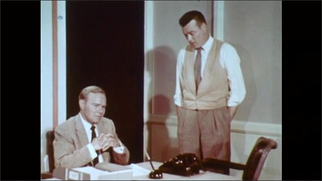 1960s: UNITED STATES: man sits at desk. Two men talk in office. Man stands by chair in office. Man stands with hands in pocket.