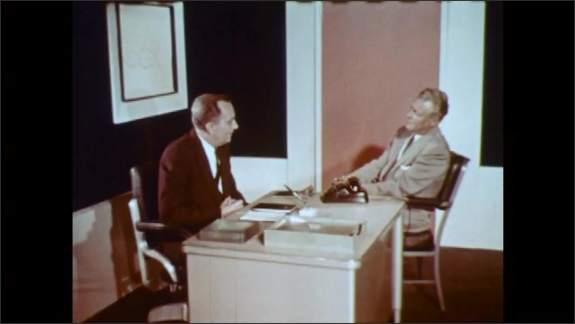1960s: UNITED STATES: two men talk in office at desk. Man helps colleague.