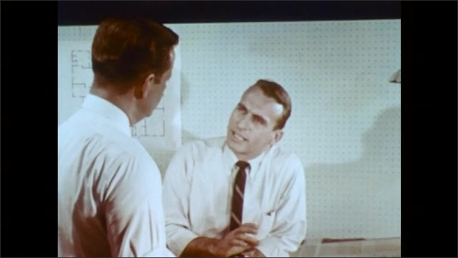1960s: UNITED STATES: colleagues talk about paper. Man talks to colleague in office