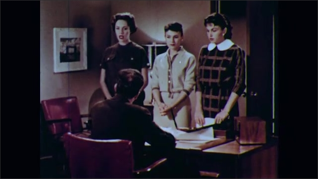 1950s: Man sitting at desk talks to three women standing in front of desk, in office.