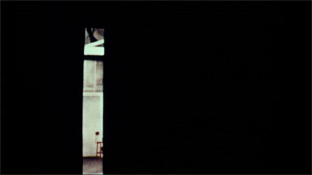 1960s: girl standing on platform puts on cap as spotlight shines on her next to small room with door, door opens, closes, leaves room in darkness, upside-down image of girl adjusting cap