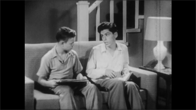 1950s: Two teen boys sit on couch, talk, look at books. Boys get up from couch, walk away. Boy walks through meadow, picks leaves.