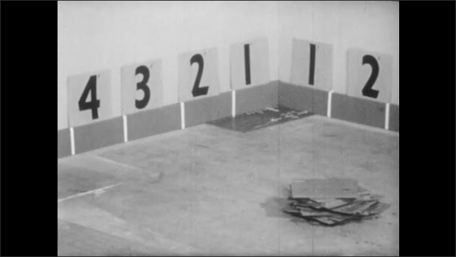 1950s: Empty kitchen with numbers marking off square feet or area. Tiles are laid down and counted along one side of the wall.